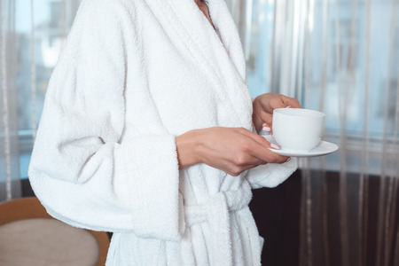 close-up partial view of woman in bathrobe holding cup of coffee and saucer