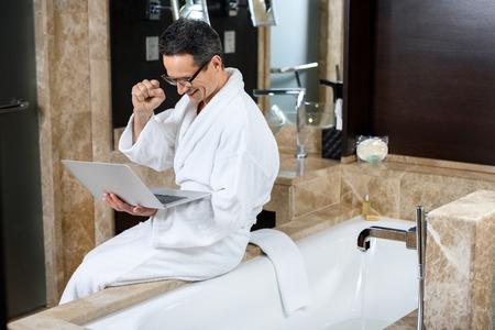 Businessman wearing a bathrobe in hotel bathroom, using his laptop while sitting on bathtub