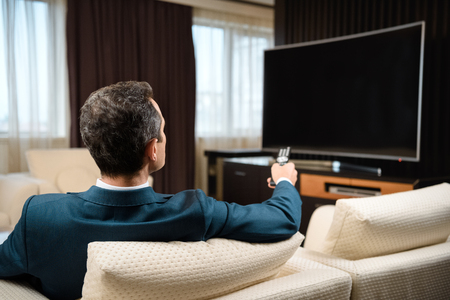 Businessman in formal suit sitting on sofa in hotel room and watching television