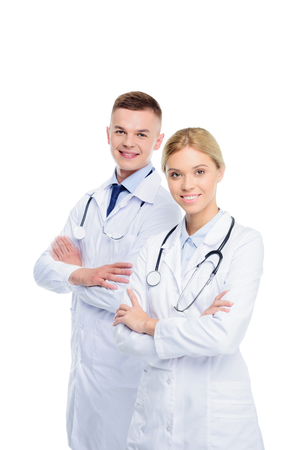 male and female doctors in white coats with stethoscopes and crossed arms, isolated on white