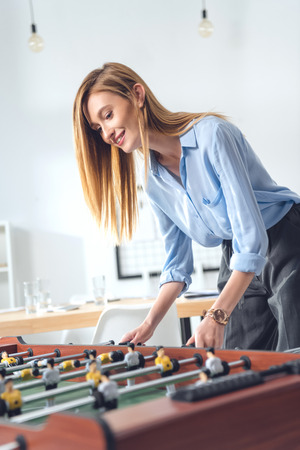 young attractive businesswoman playing table football in modern office