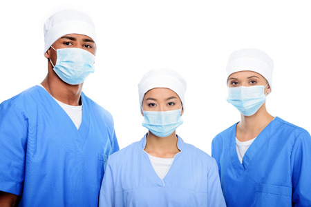 multiethnic surgeons in medical masks and caps, isolated on white