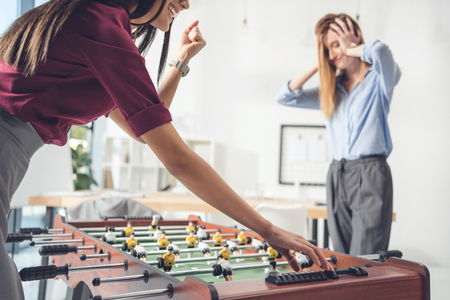 businesswomen playing table football in modern office