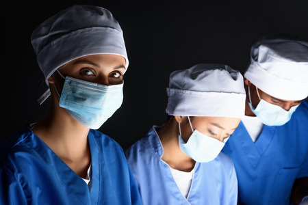 multiethnic surgeons in medical masks on operation, isolated on black