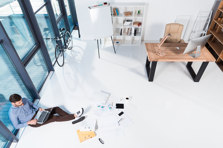 high angle view of businessman working with laptop and papers while sitting on floor in office