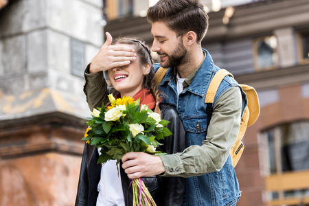 portrait of young man surprising girlfriend with bouquet of flowers on street Stock fotó
