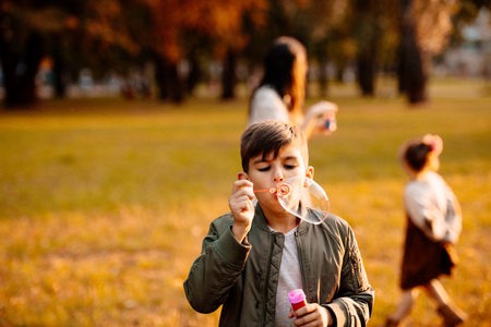 Little boy in an autumn jacket playing with soap bubbles in park