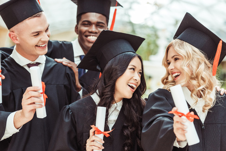 group of multiethnic students in graduation costumes with diplomas 写真素材