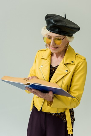 fashionable senior woman in yellow leather jacket reading book, isolated on grey Stock Photo