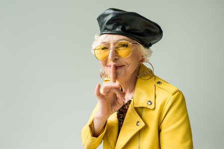 stylish senior woman in yellow jacket and leather beret with silence symbol, isolated on grey 版權商用圖片