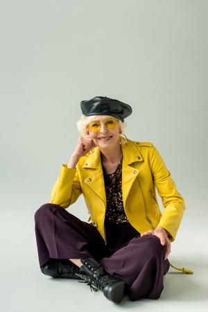stylish senior lady in yellow jacket and leather beret, isolated on grey Stock Photo