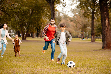 Family with two children running and playing soccer together in an autumn park Stock Photo