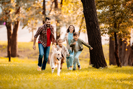 Happy family with two children running after a dog together in autumn park Foto de archivo