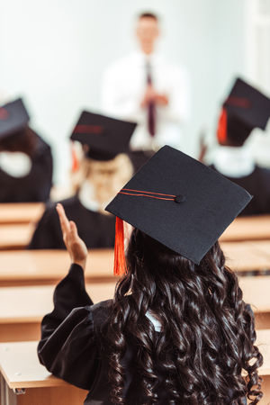 back view of student girl in graduation hat clapping hands while sitting at class