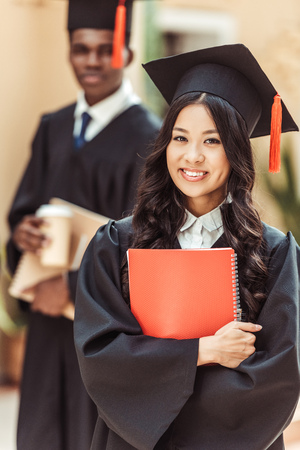 young happy asian student girl in graduation costume