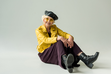 stylish senior woman in yellow jacket and leather beret, isolated on grey