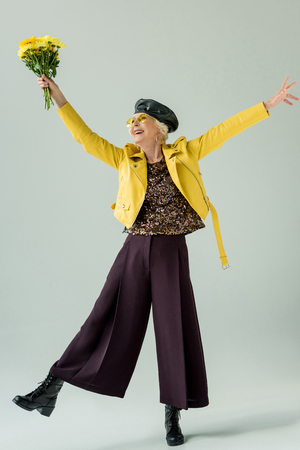 excited senior woman in yellow leather jacket with bouquet of yellow flowers, isolated on grey Stock Photo