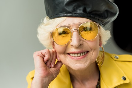 beautiful stylish senior lady in yellow sunglasses and leather beret, isolated on grey