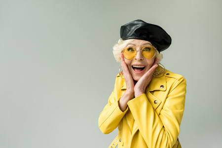 stylish excited senior woman in yellow jacket and leather beret, isolated on grey
