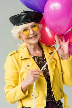 stylish senior woman in yellow jacket with colorful balloons, isolated on grey Stock Photo
