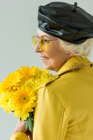 stylish senior woman in yellow jacket with bouquet of yellow flowers, isolated on grey Stock Photo