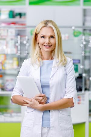 female pharmacist in white coat holding digital tablet and smiling at camera  版權商用圖片