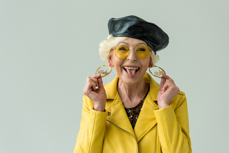 stylish senior woman in yellow leather jacket, earrings and yellow sunglasses, isolated on grey
