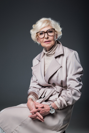beautiful senior lady in trench coat, isolated on grey