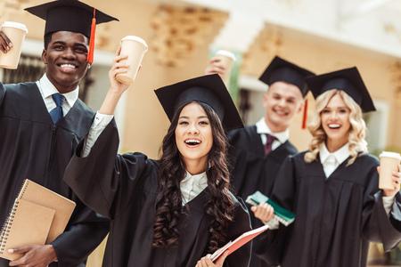 Grupo de estudiantes graduados multiétnicos con tazas de café de papel