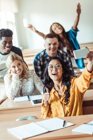 group of happy multiethnic students taking selfie in classroom Stock Photo