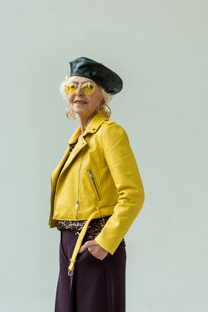 stylish senior woman in yellow leather jacket and yellow sunglasses, isolated on grey