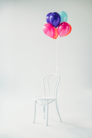 colorful balloons tied to chair, isolated on grey