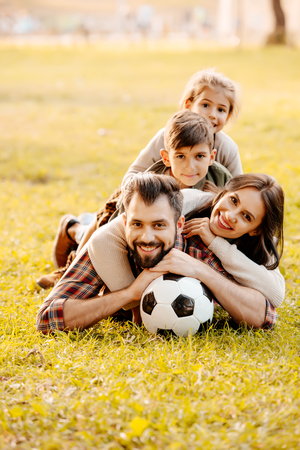 Happy family with two children lying in a pile on grass in a park Archivio Fotografico