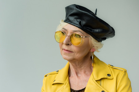 fashionable senior woman in yellow leather jacket, beret and yellow sunglasses, isolated on grey