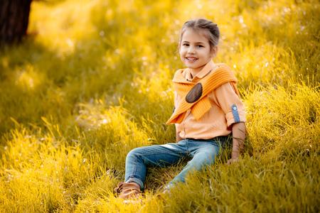 Little smiling child sitting on autumn grass