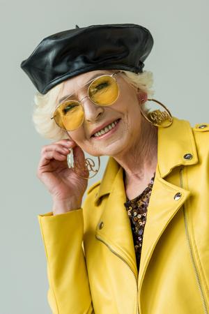 stylish senior woman in yellow leather jacket, isolated on grey