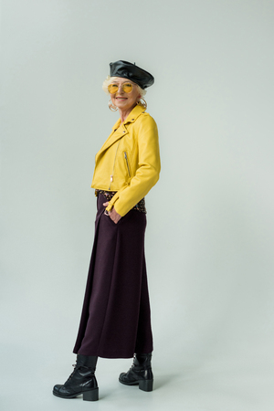 fashionable senior woman in yellow leather jacket and yellow sunglasses, isolated on grey