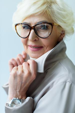 beautiful stylish senior lady in trench coat and eyeglasses, isolated on grey
