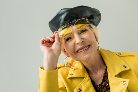 stylish senior woman in yellow sunglasses and leather beret, isolated on grey Stock Photo