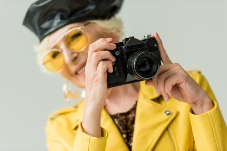 stylish senior woman in yellow jacket and leather beret taking photo on camera, isolated on grey