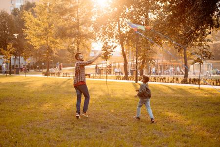 Vater und Sohn spielen mit einem Drachen in einem Herbstpark an einem sonnigen Tag
