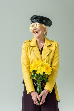 stylish senior woman in yellow leather jacket with bouquet of yellow flowers, isolated on grey