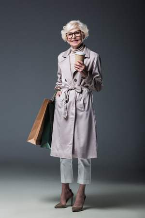 beautiful senior lady in trench coat holding shopping bags and coffee to go, on grey