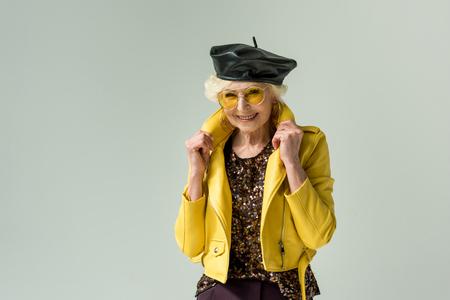 stylish senior lady posing in yellow jacket and leather beret, isolated on grey Stock Photo