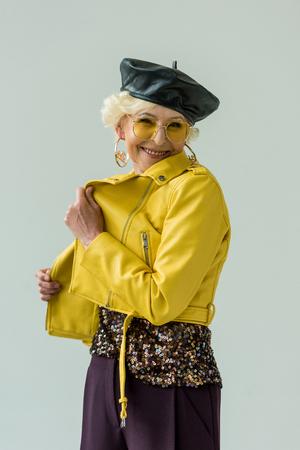 stylish senior woman in yellow leather jacket and beret, isolated on grey Stock Photo
