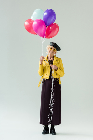 stylish senior woman in yellow leather jacket with colorful balloons, isolated on grey Stock Photo
