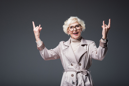 attractive senior lady in trench coat and eyeglasses showing rock signs, isolated on grey Stock Photo