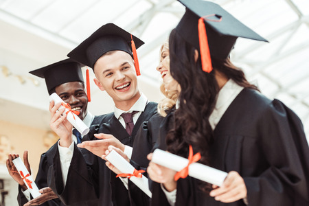 laughing graduated multiethnic students with diplomas 免版税图像 - 102320292
