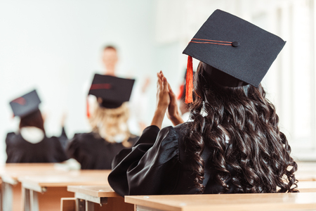 back view of student girl in graduation costume clapping hands while sitting at class