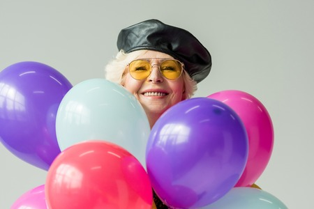 stylish senior woman in leather beret with colorful balloons, isolated on grey